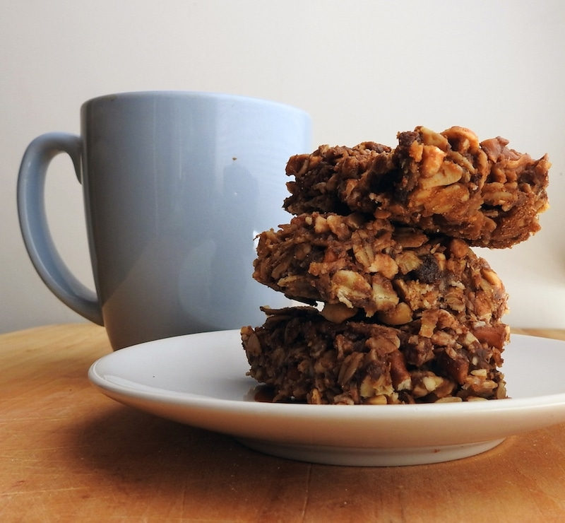 stack of three granola bars on a plate next to a coffee mug