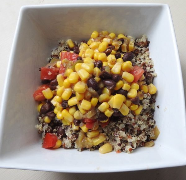 salad of corn, beans and tomatoes on bed of quinoa in square bowl